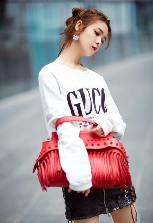 演员陈瑶白色卫衣混搭机车皮裙手持红包街头范写真图片
